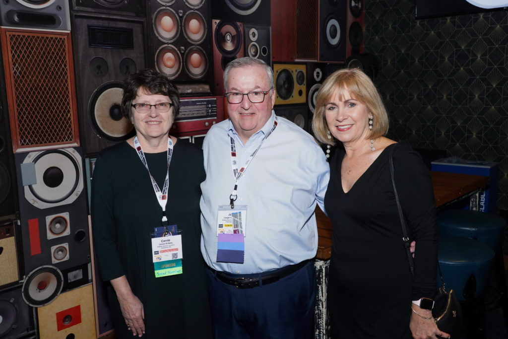 Joe McNally, center, with his wife Carole (left) and Alesa McArthur (right) at he 2019 NAEC Annual Convention in Grand Rapids, Michigan, after Joe accepted NAEC's Sturgeon Award.