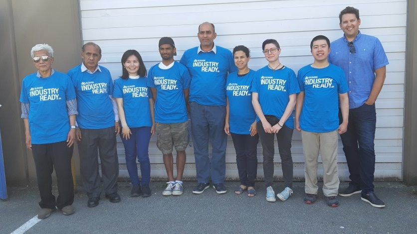 BSIABC Warehouse Certification Program graduates standing in blue shirts in front of a wall