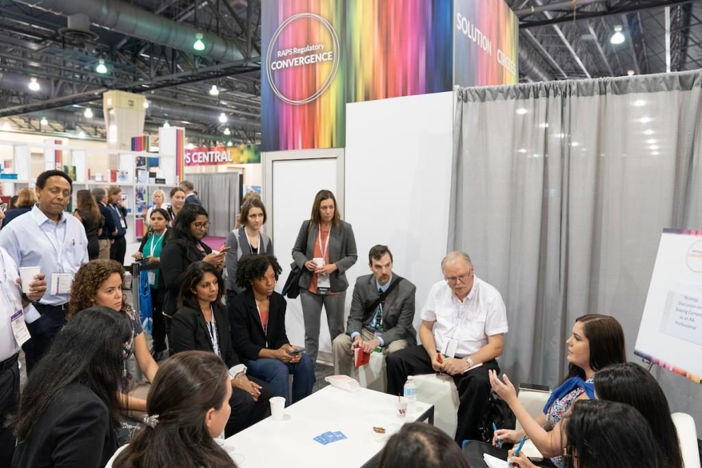 A group of regulatory professionals listen to a speaker in an informal gathering on the show floor of the 2019 RAPS Convention.