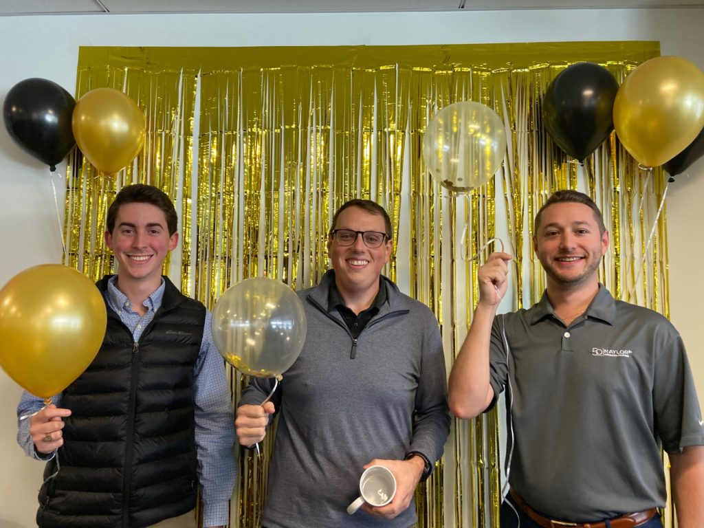 3 men standing in front of a gold curtain, holding balloons