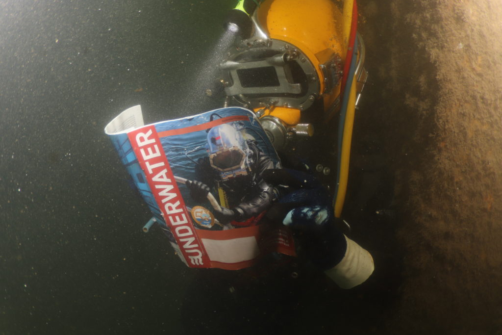 Diver in full diving gear reading a magazine under water