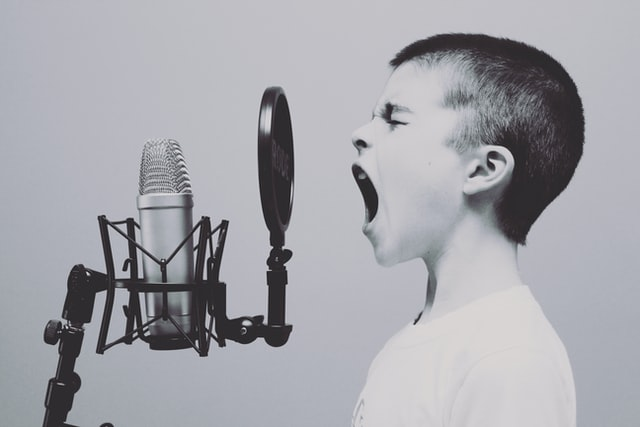 Boy screaming into microphone by Jason Rosewell Unsplash 640px