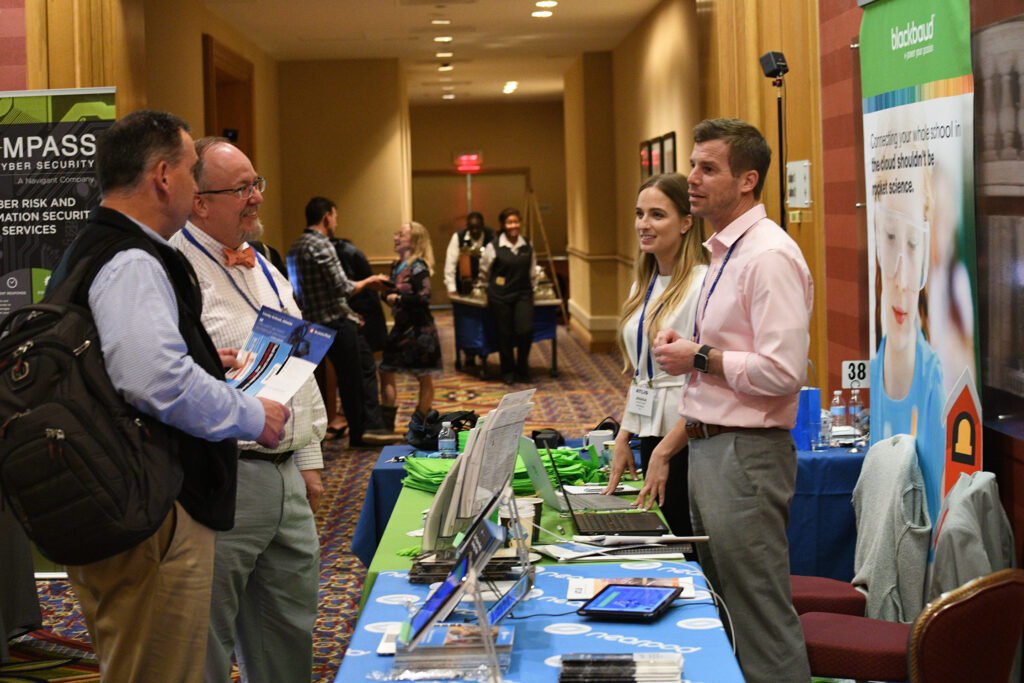 ATLIS members chat in front of a table at the 2019 ATLIS Conference