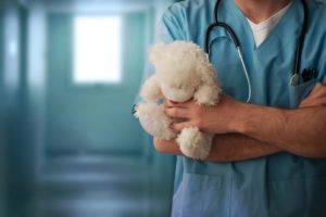 Doctor wearing a stethoscope and holding a white teddy bear